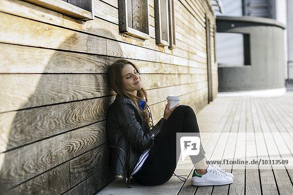 Lächelnde Frau mit Kaffee zum Sitzen auf dem Boden  an der Holzwand lehnend.