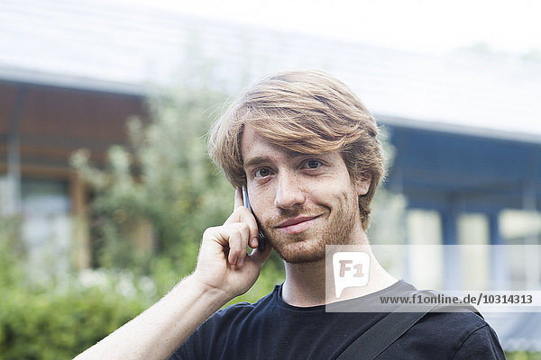 Portrait of smiling young man telephoning with smartphone