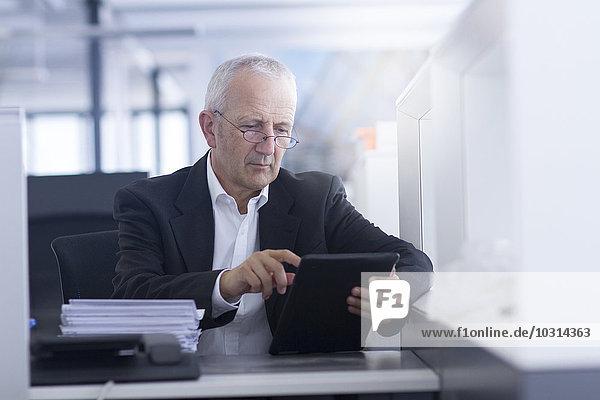 Geschäftsmann im Großraumbüro mit digitalem Tablett