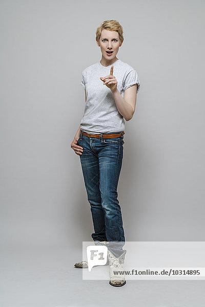 Frau mit offenem Mund und wedelndem Zeigefinger vor grauem Hintergrund stehend