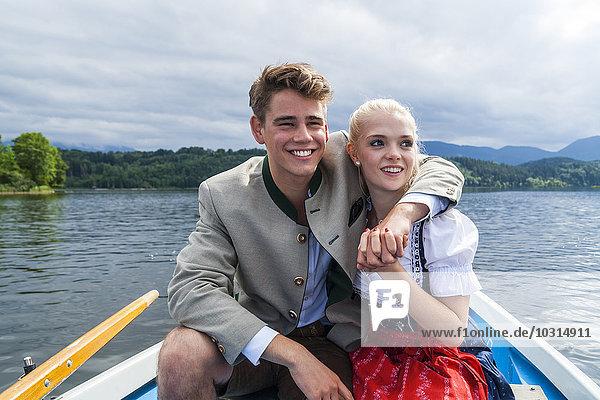 Deutschland  Bayern  Portrait eines jungen Paares im Ruderboot auf dem Staffelsee