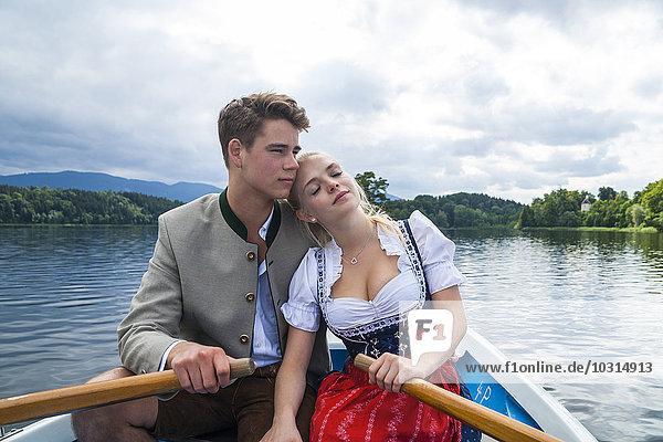 Deutschland  Bayern  junges verliebtes Paar in traditioneller Kleidung im Ruderboot auf dem Staffelsee