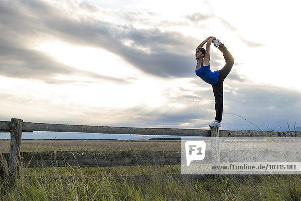Junge sportliche Frau steht auf einem Bein auf einem Tor in der Dämmerung.
