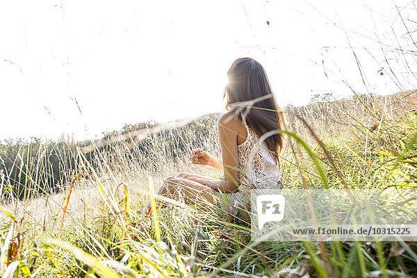 Junge Frau sitzt auf einer Wiese und genießt das Sonnenlicht