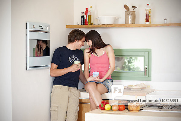 Smiling young couple face to face in the kitchen