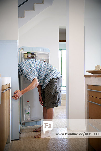 Young man standing in the kitchen searching something in the fridge