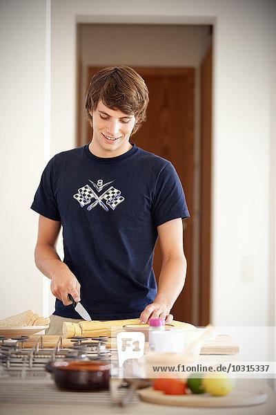Junger Mann schneidet Baguette in der Küche Junger Mann schneidet Baguette in der Küche