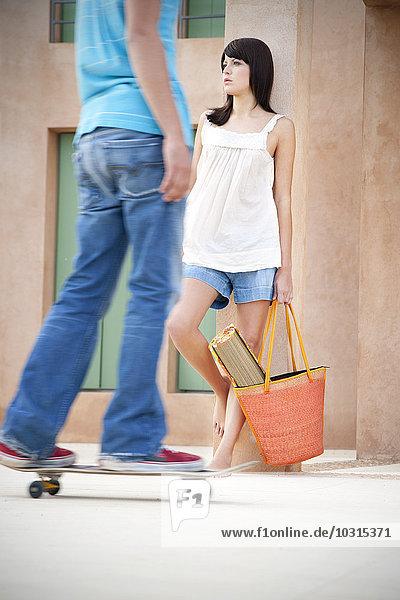 Junge Frau lehnt sich an die Säule  während junger Mann Longboarding im Vordergrund steht.