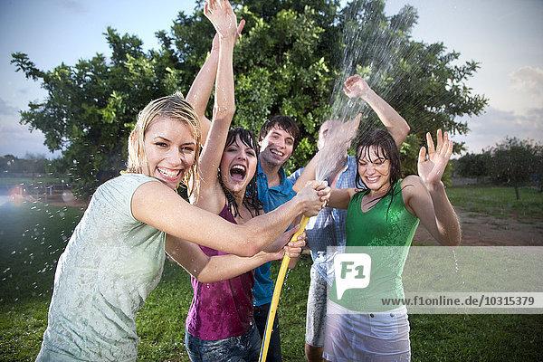 Fünf Freunde planschen mit Wasser im Garten Fünf Freunde planschen mit Wasser im Garten