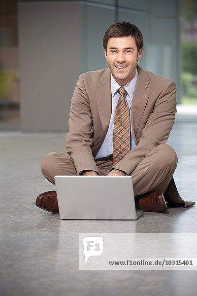 Lächelnder Geschäftsmann auf dem Boden sitzend mit Laptop Lächelnder Geschäftsmann auf dem Boden sitzend mit Laptop