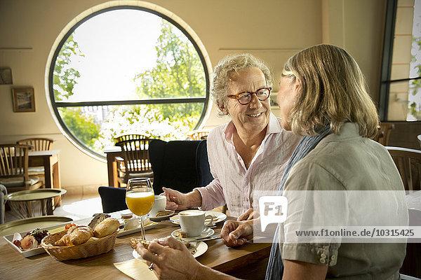 Lächelndes Seniorenpaar beim Frühstück im Cafe