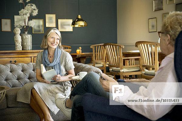 Lächelnde Seniorin auf der Couch im Aufenthaltsraum mit Blick auf den Ehemann