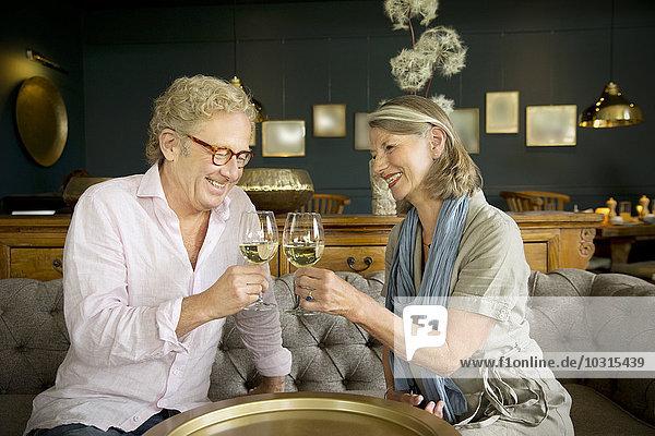 Lächelndes Seniorenpaar sitzt auf der Couch im Aufenthaltsraum und klirrende Weingläser