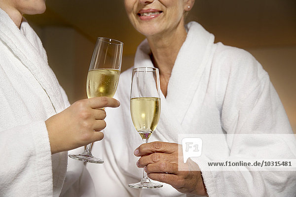 Two women in bathrobes clinking champagne glasses