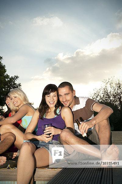 Fröhliche Freunde sitzen am Pool