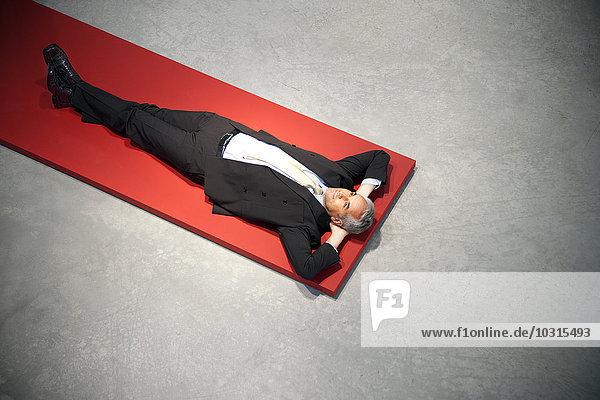 Entspannter Geschäftsmann auf dem Boden liegend Entspannter Geschäftsmann auf dem Boden liegend