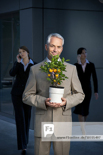 Lächelnder Geschäftsmann mit Mandarinenbaum und Geschäftsfrau im Hintergrund Lächelnder Geschäftsmann mit Mandarinenbaum und Geschäftsfrau im Hintergrund