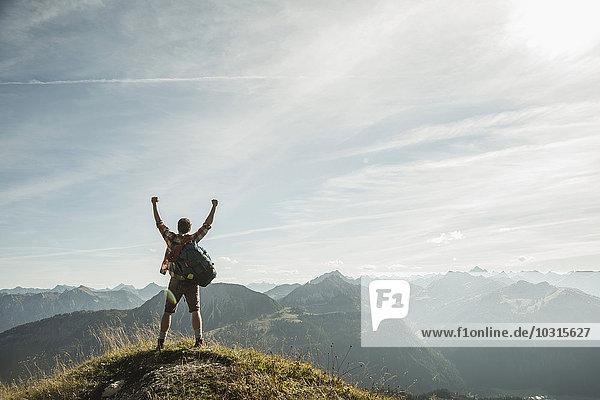 Österreich  Tirol  Tannheimer Tal  junger Mann jubelt auf den Berggipfel