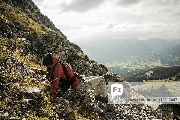 Österreich  Tirol  Tannheimer Tal  junge Wanderin beim Ausruhen in den Bergen