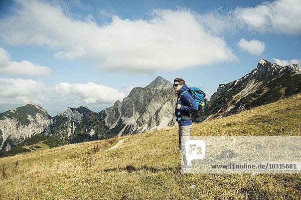 Austria  Tyrol  Tannheimer Tal  hiker with backpack on alpine meadow