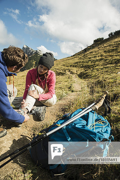 Austria  Tyrol  Tannheimer Tal  young man caring for injured woman on hiking tour