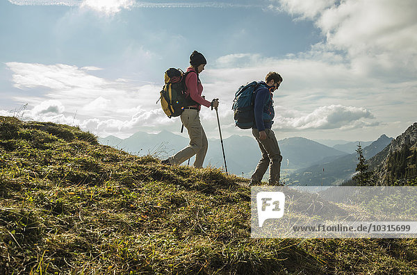 Österreich,  Tirol,  Tannheimer Tal,  junges Paar beim Wandern auf Almen