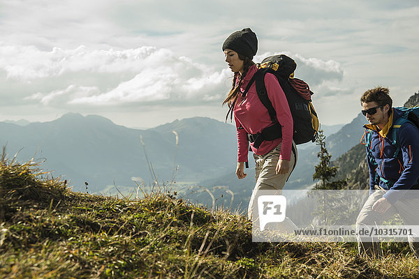 Austria  Tyrol  Tannheimer Tal  young couple hiking on alpine meadow