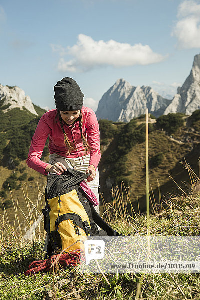 Austria  Tyrol  Tannheimer Tal  female hiker with backpack on alpine meadow