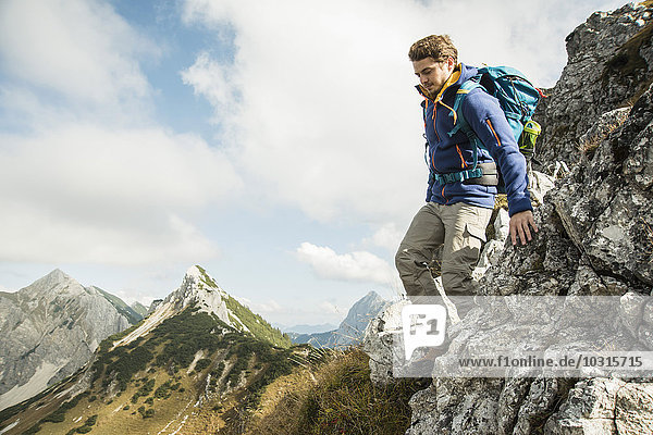 Austria  Tyrol  Tannheimer Tal  young man hiking on rock