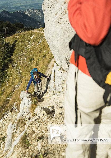 Austria,  Tyrol,  Tannheimer Tal,  young couple hiking on rock
