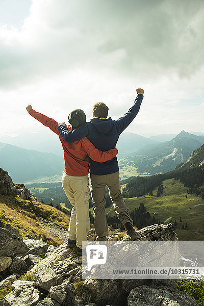 Austria  Tyrol  Tannheimer Tal  young couple cheering on mountain top