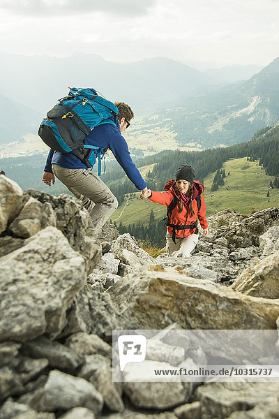 Austria,  Tyrol,  Tannheimer Tal,  young couple hiking on rocks