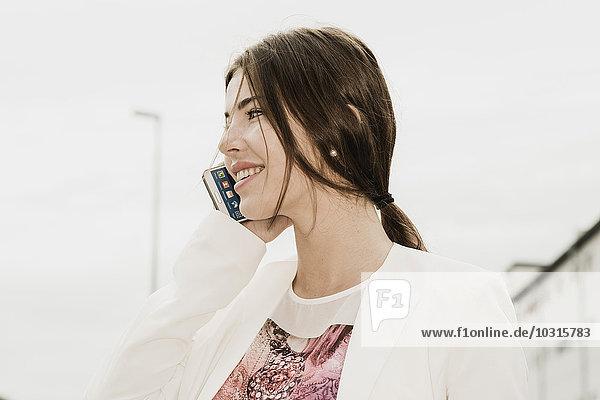 Lächelnde junge Geschäftsfrau telefoniert mit Smartphone