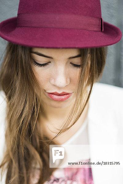 Junge Frau mit langem braunem Haar und Hut