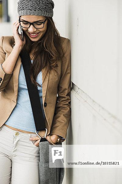 Lächelnde junge Frau telefoniert mit einem an die Wand gelehnten Smartphone