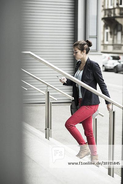 Junge Geschäftsfrau mit Smartphone im Obergeschoss