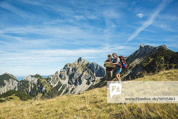 Austria  Tyrol  Tannheimer Tal  young hikers looking at map