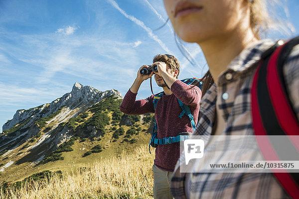Austria  Tyrol  Tannheimer Tal  young man on hiking trip looking through binocular