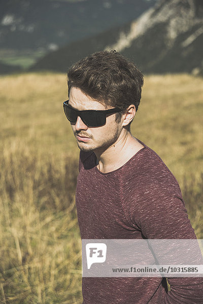 Austria  Tyrol  Tannheimer Tal  young man wearing sunglasses outdoors
