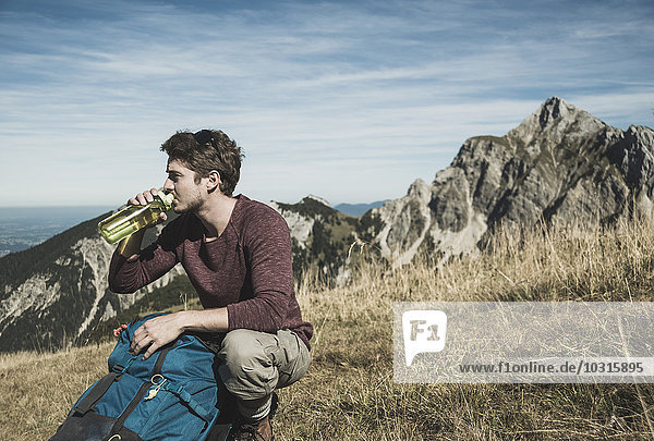 Österreich  Tirol  Tannheimer Tal  junger Mann mit Rucksack und Trinkflasche auf Almwiese