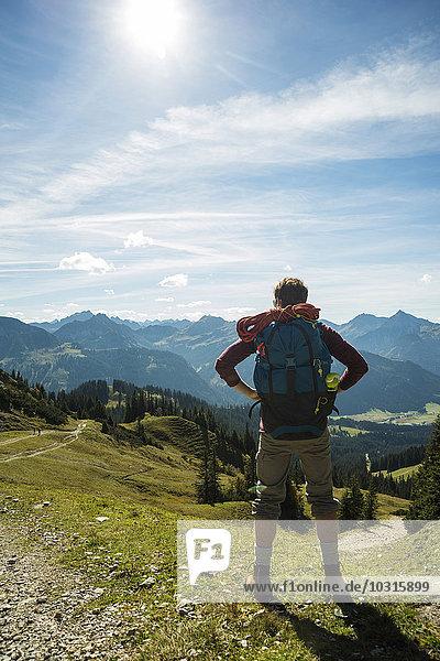 Österreich  Tirol  Tannheimer Tal  junger Mann in den Bergen mit Blick auf die Berge