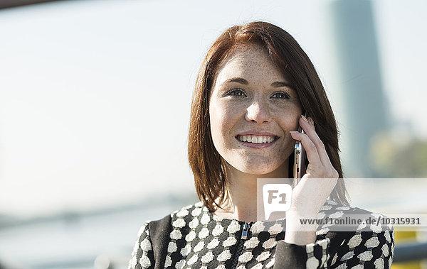 Lächelnde brünette junge Frau am Handy