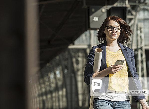 Junge Frau mit Handy am Bahnhof