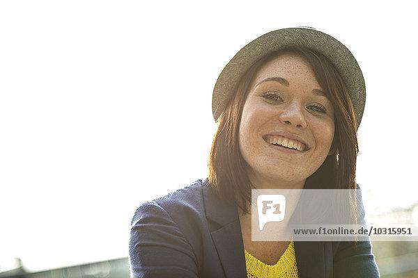 Porträt einer lächelnden jungen Frau mit Hut