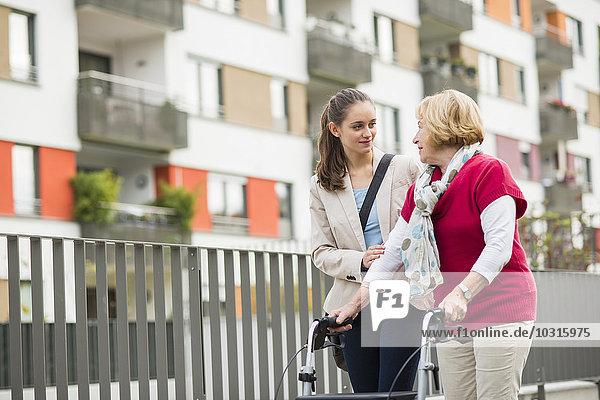 Enkelin  die ihrer Großmutter beim Laufen mit dem Rollator hilft