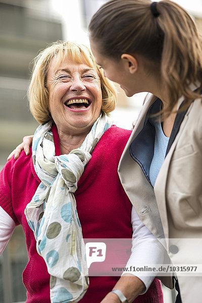 Porträt einer lachenden Seniorin  die mit ihrer Enkelin kommuniziert.
