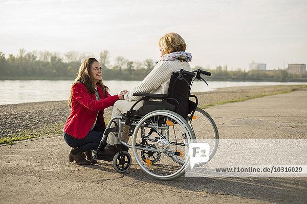 Erwachsene Enkelin  die ihrer Großmutter im Rollstuhl assistiert
