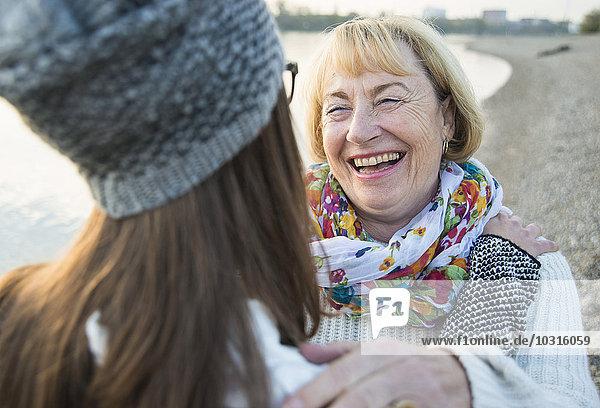 Porträt der lächelnden blonden Seniorin von Angesicht zu Angesicht zu ihrer Enkelin