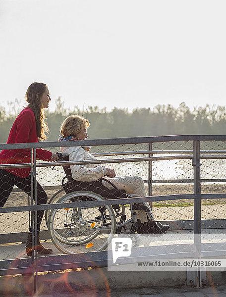Enkelin  die ihrer Großmutter im Rollstuhl assistiert