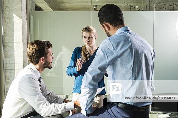 Drei junge Geschäftsleute diskutieren im Büro